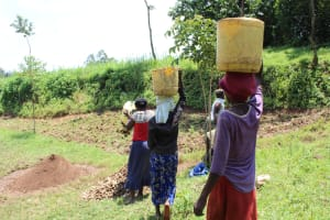 The Water Project: Emmachembe Community, Magina Spring -  Community Members Bringing Materials To Site