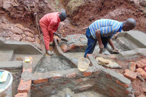 The Water Project: Hirumbi Community, Khalembi Spring -  Pipe Is Set Rub Wall Gets Cement