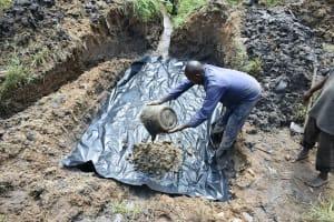 The Water Project: Sichinji Community, Kubai Spring -  Adding Concrete To Spring Foundation
