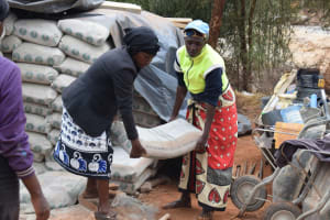 The Water Project: Mukuku Community -  Lifting Cement Bag