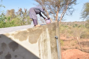 The Water Project: Katalwa Secondary School -  Wetting Cement To Help Cure