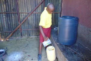The Water Project: Givudemesi Primary School -  Student Collecting Water From Home