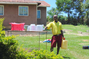 The Water Project: Givudemesi Primary School -  A Boy Collects Water At Home