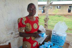 The Water Project: Lwombei Primary School -  Senior Teacher Phinora Khanali Unpacking Feminine Hygiene Towels For Students