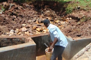 The Water Project: Ebutindi Community, Tondolo Spring -  Backfilling With Stones As Water Starts To Flow