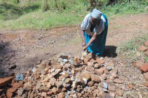 The Water Project: Bumavi Community, Joseph Njajula Spring -  Elderly Woman Helps Crush Rocks To Gravel