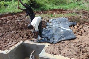 The Water Project: Bumavi Community, Joseph Njajula Spring -  Backfilling With Soil And Plastic Tarp