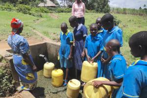 The Water Project: St. Michael Mukongolo Primary School -  Students Fetch Water Alongside Community Member