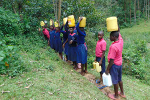 The Water Project: Jinjini Friends Primary School -  Students Carrying Water