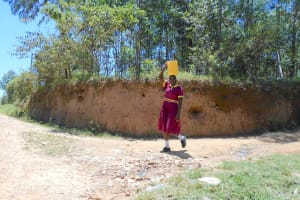 The Water Project: Givudemesi Primary School -  Student Carrying Water From Home
