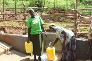 The Water Project: Bumavi Community, Joseph Njajula Spring -  Women Smile While Fetching Water