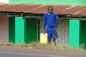 The Water Project: Boyani Primary School -  Student Waiting To Cross The Road With Water