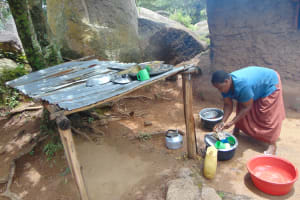 The Water Project: Gidimo Primary School -  School Cook Washing Dishes Next To The Dishrack
