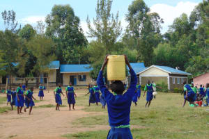 The Water Project: Boyani Primary School -  Student Carrying Water To School