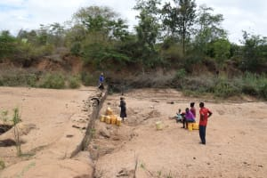 The Water Project: Kiteta Community A -  Community Members Get Water At A River Scoop Hole