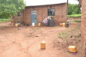 The Water Project: Mbitini Community -  Getting Water From Water Storage Containers