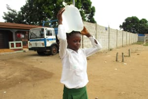 The Water Project: Lungi, Kasongha, DEC Kasongha Primary School -  Pupil Carrying Water