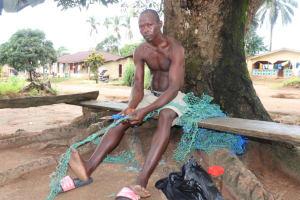 The Water Project: Lungi, Mahera, Mahera Health Clinic -  Young Man Making Fishing Net