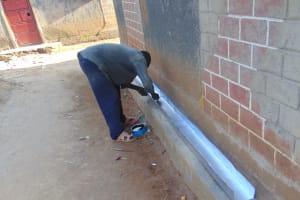 The Water Project: Nanganda Primary School -  Artisan Prepares The Gutter