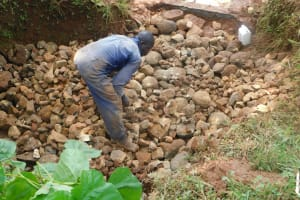 The Water Project: Emulembo Community, Gideon Spring -  Backfilling With Stones Continues