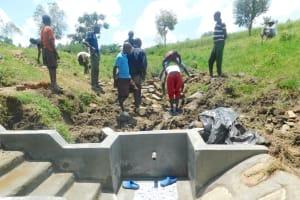 The Water Project: Sambaka Community, Sambaka Spring -  Community Helps Backfill With Large Stones