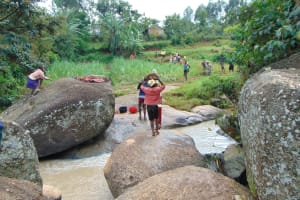 The Water Project: Munenga Community, Francis Were Spring -  Community Members Carry Rocks To Construction Site