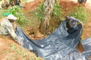 The Water Project: Emulembo Community, Gideon Spring -  Adding Plastic Tarp Over Backfilled Stones