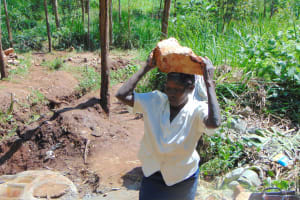 The Water Project: Masuveni Community, Masuveni Spring -  Community Member Delivers Stone To Spring Site