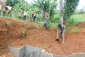 The Water Project: Emulembo Community, Gideon Spring -  Filling In Backfilled Area With Soil