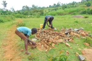 The Water Project: Munenga Community, Francis Were Spring -  Community Members Break Down Rocks For Construction