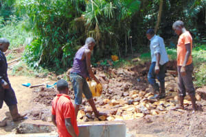The Water Project: Masuveni Community, Masuveni Spring -  Backfilling Spring Box With Stones
