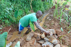 The Water Project: Munenga Community, Francis Were Spring -  Backfilling With Large Stones