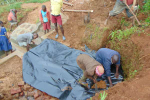 The Water Project: Munenga Community, Francis Were Spring -  Covering Stone Backfill With Thick Plastic Tarp