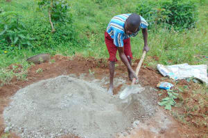 The Water Project: Munenga Community, Francis Were Spring -  A Boy Helps Mix Cement