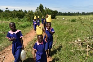The Water Project: Eshimuli Primary School -  Students Carry Water Back To School