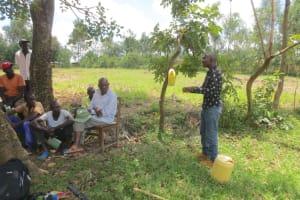 The Water Project: Sambaka Community, Sambaka Spring -  Facilitator Demonstrating Leaky Tin Use For Handwashing