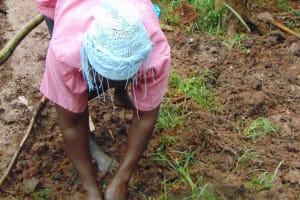 The Water Project: Masuveni Community, Masuveni Spring -  Community Member Helps Plant Grass