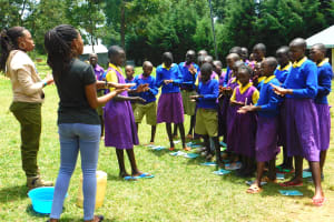 The Water Project: Kapkures Primary School -  Student Helps Lead The Demonstration