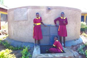 The Water Project: Nanganda Primary School -  Girls Pose With The Rain Tank