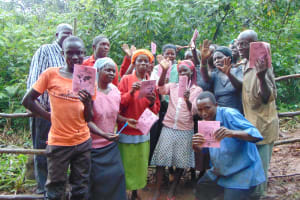 The Water Project: Masuveni Community, Masuveni Spring -  Showing Off Booklets After Completing Training