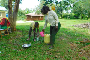 The Water Project: Bumira Community, Madegwa Spring -  Trainer Laura Pouring Water For Hanwashing Demonstration With A Child