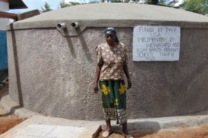 The Water Project: Banja Primary School -  The School Cook Posing With The Tank