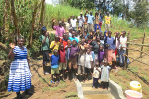 The Water Project: Sambaka Community, Sambaka Spring -  Community Members With Field Officer Betty Majani Pose On The Spring Stairs