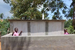 The Water Project: Banja Primary School -  Thumbs Up From Behind Boys Latrine Wall