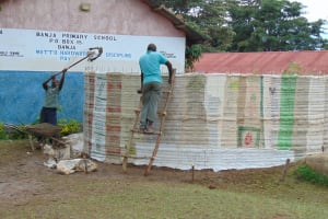 The Water Project: Banja Primary School -  Shoveling Cement Mix Into Tank