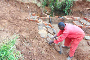 The Water Project: Munenga Community, Francis Were Spring -  Rub Wall Construction