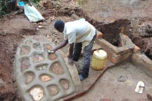 The Water Project: Masuveni Community, Masuveni Spring -  Cementing The Rub Wall
