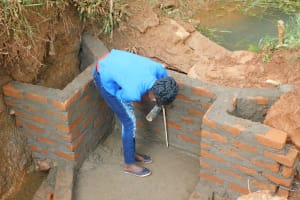 The Water Project: Emulembo Community, Gideon Spring -  Field Officer Elvin Confirming Accurate Measurements