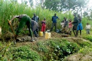 The Water Project: Sambaka Community, Sambaka Spring -  Community Member Slook On As Artisans Mix Cement
