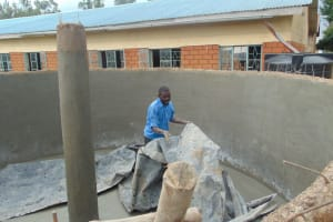 The Water Project: Demesi Primary School -  Removing Protective Tarps From Inside Tank